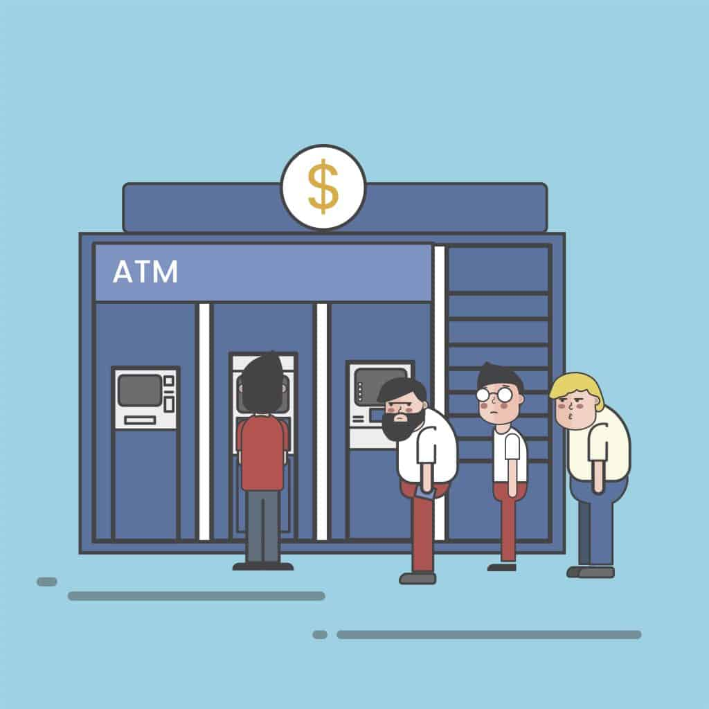 Three men lining up at the ATM waiting for one to finish withdrawing money.