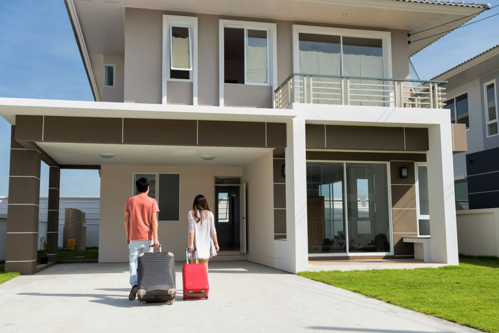 Young couple moving into a home with luggage after getting a Foreigner Loan Singapore